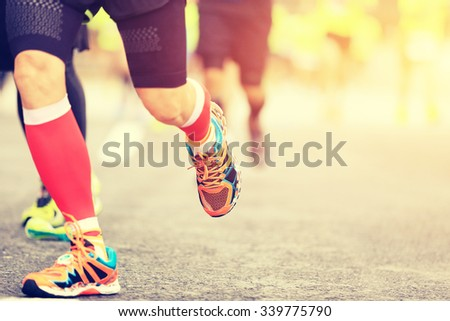 marathon runners legs running on city road - stock photo