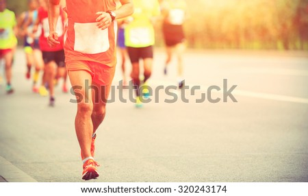 Marathon runners running on city road - stock photo