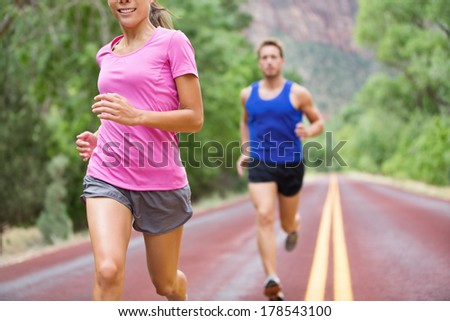 Marathon running athletes couple training on road. Fitness runners, man and woman jogging in active lifestyle. - stock photo