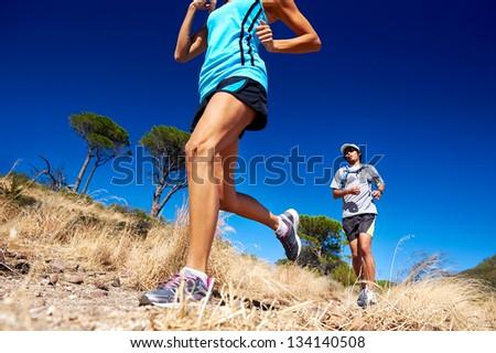 marathon running athletes couple training on trail fitness sport active lifestyle - stock photo