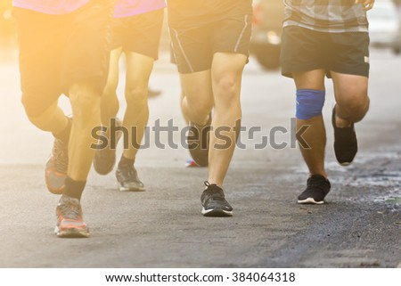 Marathon running race people competing in fitness and healthy active lifestyle feet on road in the morning. - stock photo