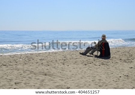 MARBELLA, SPAIN - APRIL 9: Man reading  at the shore of the sea in Marbella, Spain on April 9, 2016.
