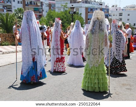 MARBELLA, SPAIN - JUNE 11, 2008 - Spanish women in traditional dresses walking through the street during the Romeria San Bernabe, Marbella, Costa del Sol, Andalusia, Spain, June 11, 2008. - stock photo