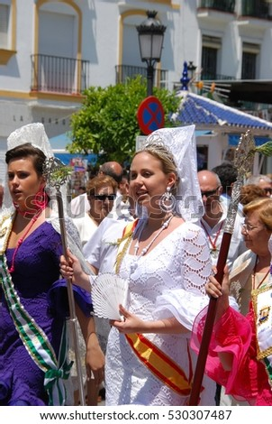 MARBELLA, SPAIN - JUNE 11, 2008 - Spanish women in traditional dresses walking through the street during the Romeria San Bernabe, Marbella, Malaga Province, Andalusia, Spain, June 11, 2008.