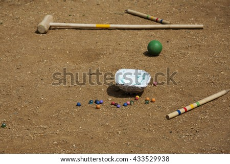 Marble balls on sand background. Croquet mallet on sand background. Playing equipment for children. Sport for children. Leisure time equipment. Coloured glass marbles. Sunny leisure time situation. - stock photo