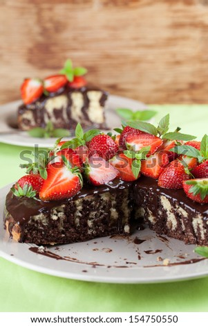 Marble cake with chocolate glaze and strawberries. Shallow dof - stock photo