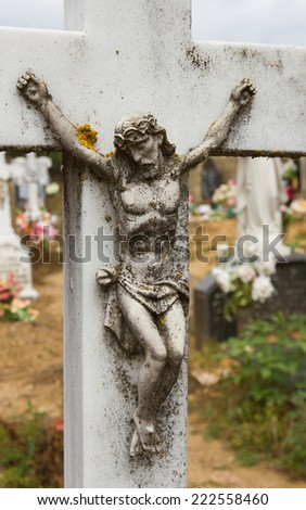 Marble figure of Christ on the cross for aging time in a cemetery - stock photo