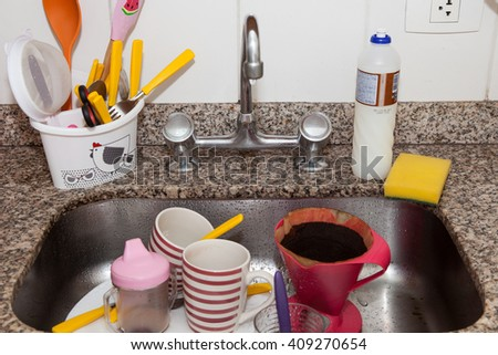 Marble sink full of dirty dishes and cleaning detergent and sponge - stock photo