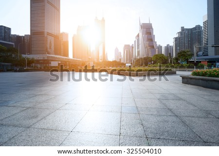 marble square under golden sunbeam with skyscrapers arounded - stock photo