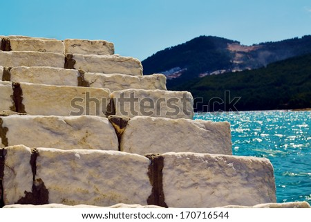 marble staircase leading up near  the sea on a summer day - stock photo