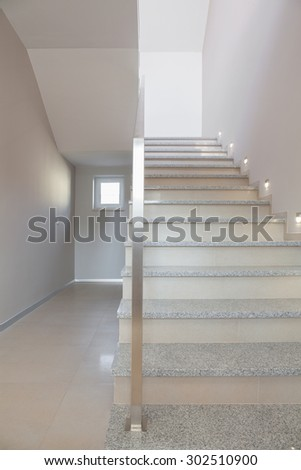 Marble stairs with steel handrail in minimalist storey house