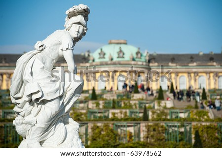 Marble statue with Sanssouci castle in the background in Potsdam, Germany