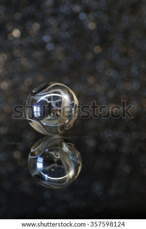 Marbles beads with Reflection on Glass, de focused light background, Artistic abstract composition (crystal sphere)                                 - stock photo