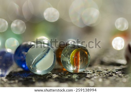 marbles in the sun,blurry. Macro, closeup. Picture taken out on the street. - stock photo