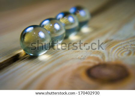 marbles on wooden table - stock photo