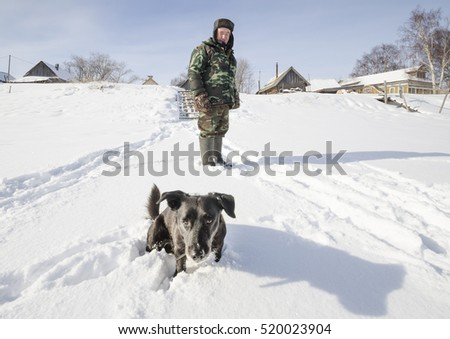 March, 2016 - Chubola-Navolok. The old man and the dog in the snow. Russia, Arkhangelsk Oblast, Primorsky district, village Chubola-Navolok