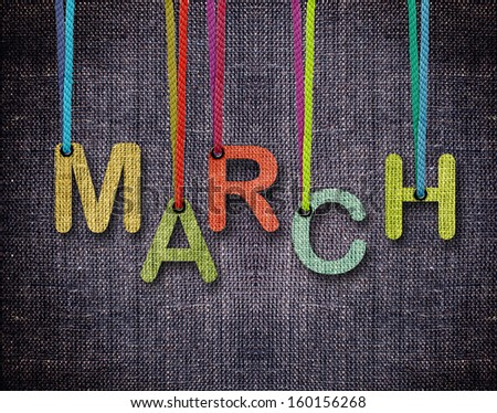 March letters hanging strings with blue sackcloth background. - stock photo