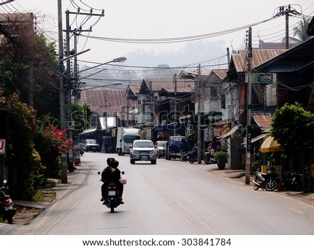 March 20, 2015: low traffic on local road street in a small town in northern THAILAND showing easy and slow life country living style in old vintage surrounding cute little province in THAILAND  - stock photo