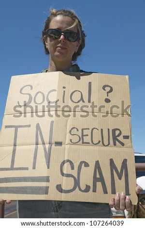 MARCH 2005 - Protestor of President George W. Bush holding a sign up protesting his Social Security plan, in Tucson Arizona
