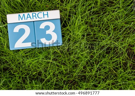 March 23rd. Day 23 of month, calendar on football green grass background. Spring time, empty space for text