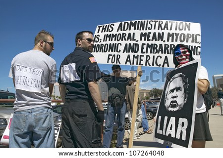 MARCH 2005 - Three protestors in Tucson, AZ of President George W. Bush is holding a sign proclaiming Bush is a Liar regarding the Iraq War - stock photo