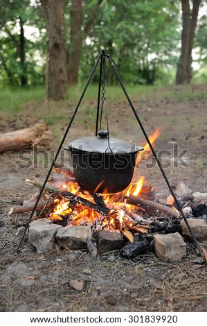 Marching kettle on the fire in the forest - stock photo
