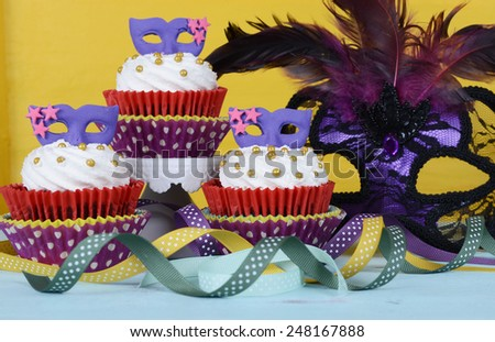 Mardi Gras cupcakes with purple mask toppers on rustic style vintage yellow and aqua blue wood background. . - stock photo