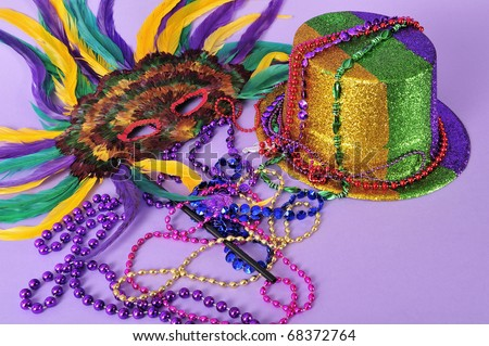 "Mardi Gras feathered masks shiny party hat Mardi Gras beads studio shot on purple background.  Copy space. Set series. ""Mardi Gras""  means ""Fat Tuesday"" the day to indulge before Lent begins. - stock photo"
