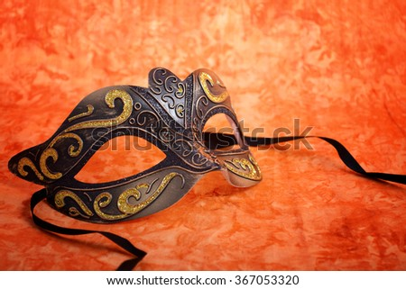 Mardi Gras mask on a bright, colorful orange background, closeup.   - stock photo