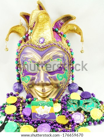 Mardi Gras mask with beads and doubloons. - stock photo