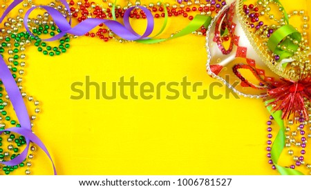 Mardi Gras overhead background with colorful masks and beads on rustic yellow wood background, with copy space.