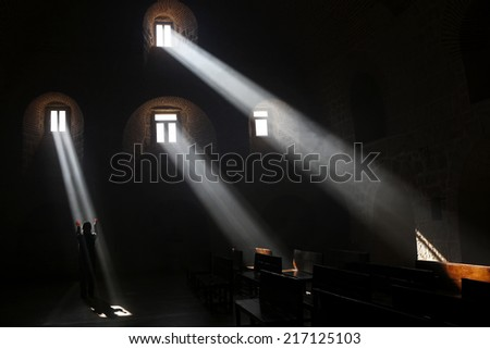 Mardin,Turkey- 05/02/2014 : St.Gabriel Monastery and a muslim woman praying under the light beams in the morning