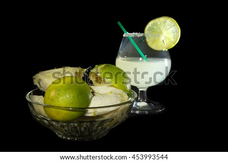Margarita cocktail and a plate of squashed lime on the black background