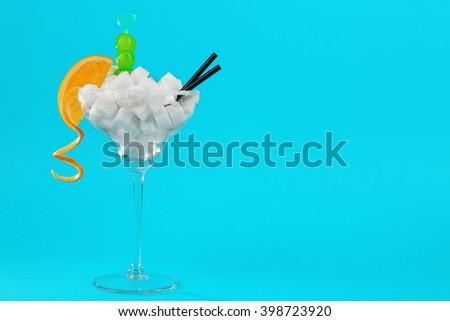 Margarita glass with lump sugar, cocktail straws, cherries and orange slice on blue background - stock photo