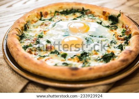 Margarita pizza with arugula and egg for breakfast, selective focus - stock photo