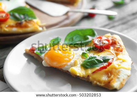 Margarita pizza with basil leaves and egg on plate closeup