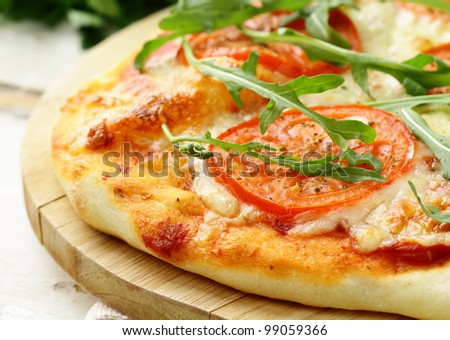 Margarita pizza with tomatoes and with arugula,  on the board