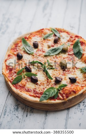 Margarita Pizza with tomatoes, mozzarella and basil with olives on wooden plate on white wooden table