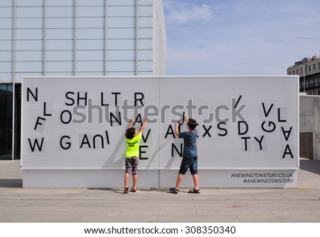 MARGATE, KENT, UK - AUGUST 15. 2015. Chldren rearange the lettering on an installation at the Turner Contemporary art gallery located at the coastal town of Margate, Kent, UK. - stock photo