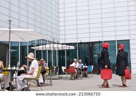MARGATE,UK-JULY25: The Red Ladies a renowned theatrical  group from Clod Ensemble, bring their performance to Margate's Turner Contemporary Gallery and sea front.July 25, 2014 in Margate, Kent UK. - stock photo
