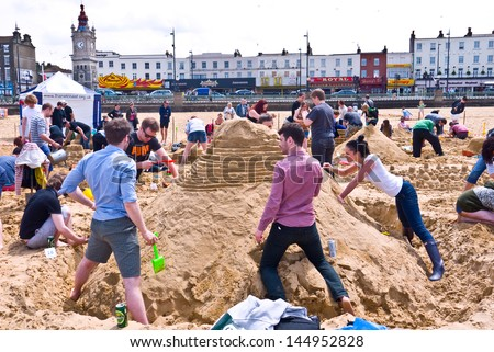 MARGATE, UK-JUNE 29: View of the teams building their sand castles in the RIBA sandcastle Challenge, on Margate's main sands watched by many visitors to the beach. June 29, 2013 Margate UK - stock photo