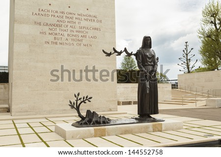 MARGRATEN - May 25: The statue at the Court of Honor welcomes visitors at Margraten War Cemetery. Part of the memorial tower is also shown, with its inscription, on May 25, 2013. - stock photo
