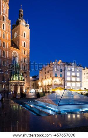 Mariacki Church in Krakow, Poland. Beautiful historical building photographed against deep blue night sky. - stock photo