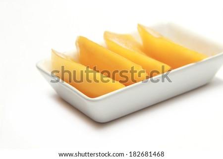 Marian plum slide in dish on white background - stock photo