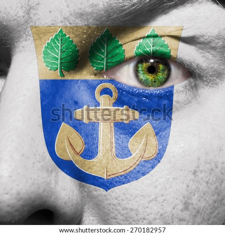 Mariehamn flag painted on a man's face to support his city Mariehamn