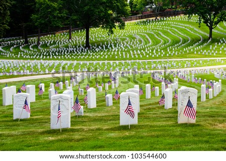 MARIETTA, GA - MAY 26: U.S. flags decorate veterans' graves on May 26, 2012, for Memorial Day at the National Cemetery in Marietta, Ga. More than 17,500 war veterans are buried at the cemetery. - stock photo