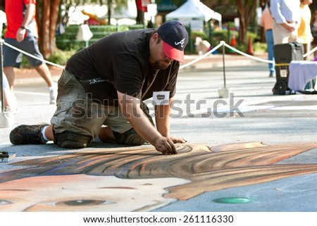 MARIETTA, GA - OCTOBER 11:  A chalk artist kneels on the pavement to draw an elaborate Halloween scene on a downtown street as part of the Marietta Chalkfest on October 11, 2014 in Marietta, GA.