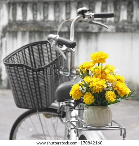 Marigold flower and retro bicycle on street - stock photo