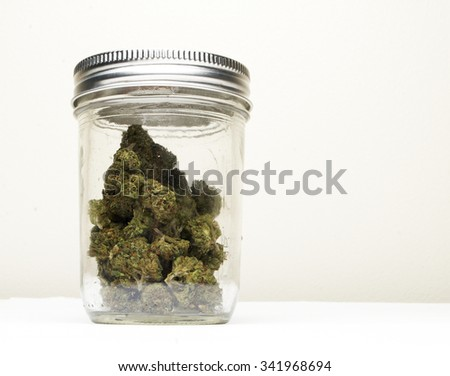 Marijuana and Cannabis in Glass Jar  - stock photo