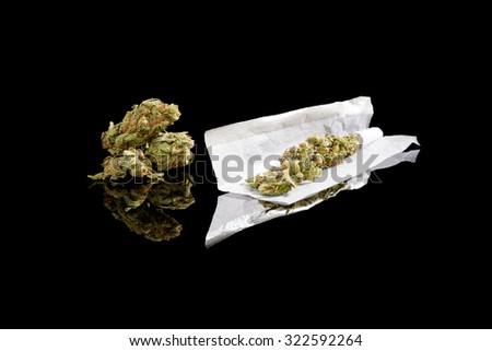 Marijuana bud and cigarette rolling paper isolated on black background. Smoking cannabis, addiction or medical use. - stock photo
